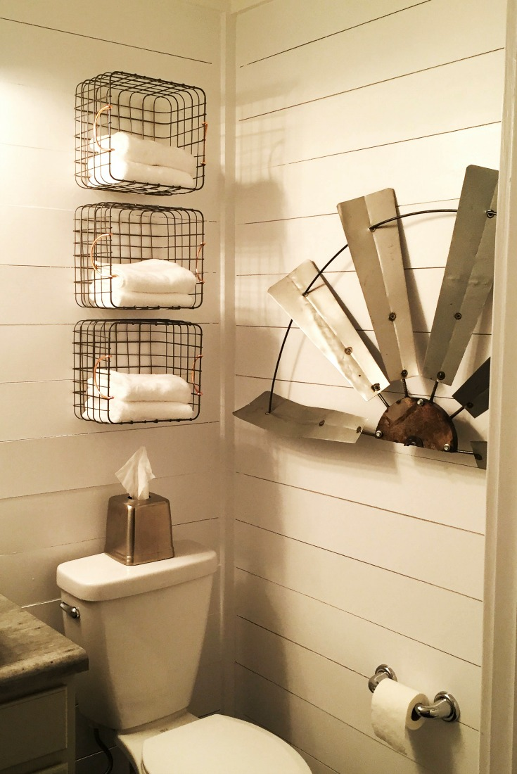 Guest bathroom remodel with shiplap walls, windmill, 3 baskets on the wall with towels in them, top of a toliet with a tissue dispenser on top.