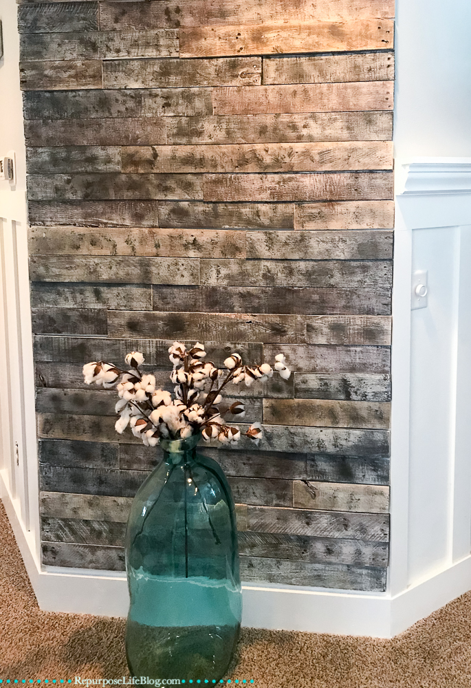 Large turquoise glass vase sitting in front of pallet board wall