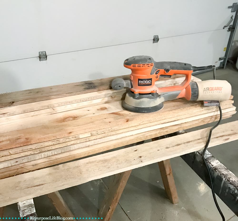 pallet boards with a Ridgid Orbital Sander on top