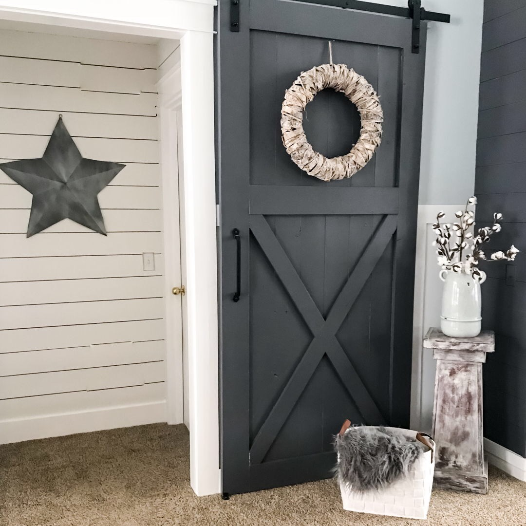 Shiplap walls in an alcove. Gray sliding barn door at alcove entryway. White basket with a gray blanket in it. Pedestal stand with a light blue vase and cotton sprigs. Board and batten walls.