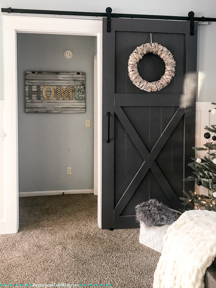 Black sliding barn door with neutral wreath and HOME sign in background