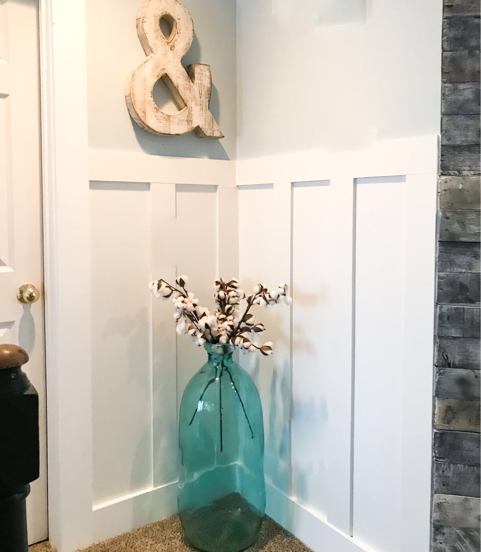 large vase with cotton in front of board and batten wall