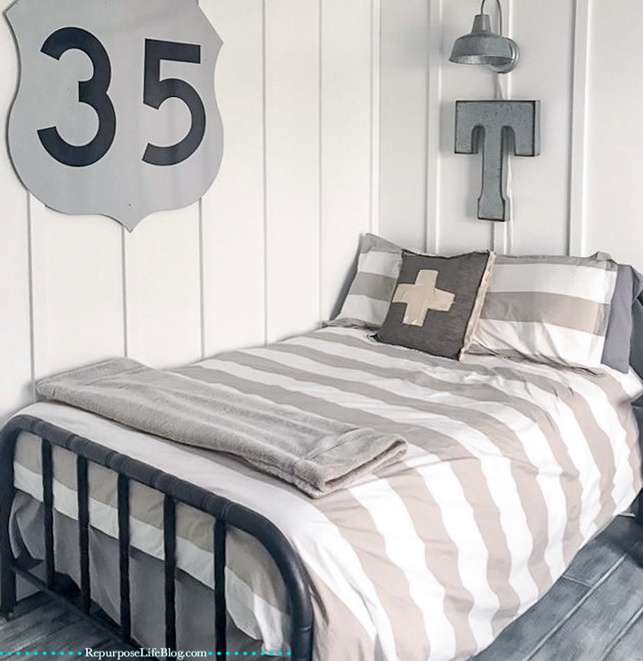 boys bedroom. Bed with gray and white striped comforter and board and batten walls in background