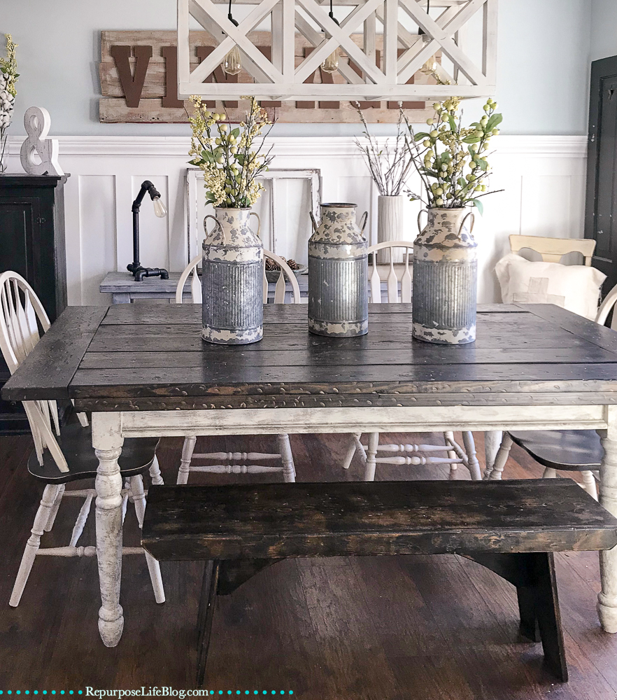 Dining room table with 3 milk canisters and floral arrangements inside them. Board and batten wall in the background