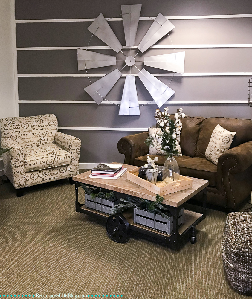 couch, chair, coffee table, windmill on a wall treatment wall.