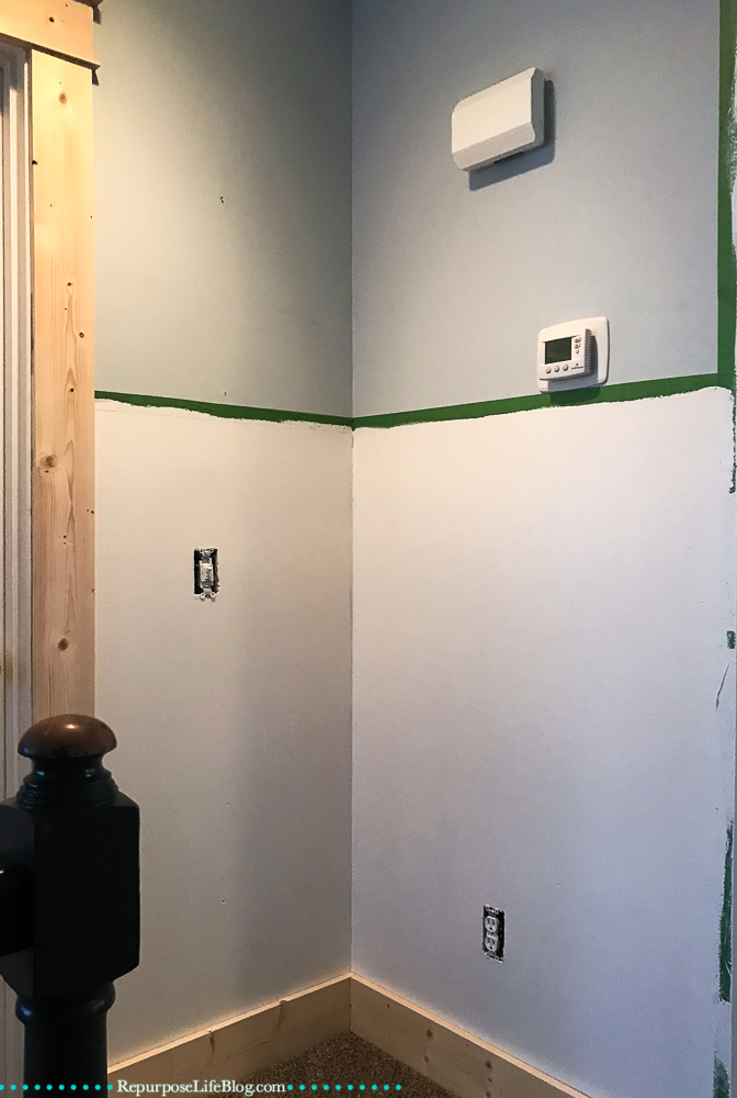 blue wall taped off and painted white on bottom