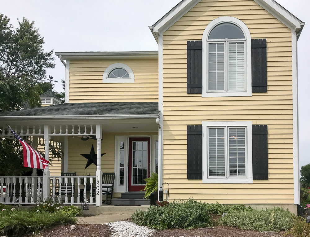 yellow house with diy shutters