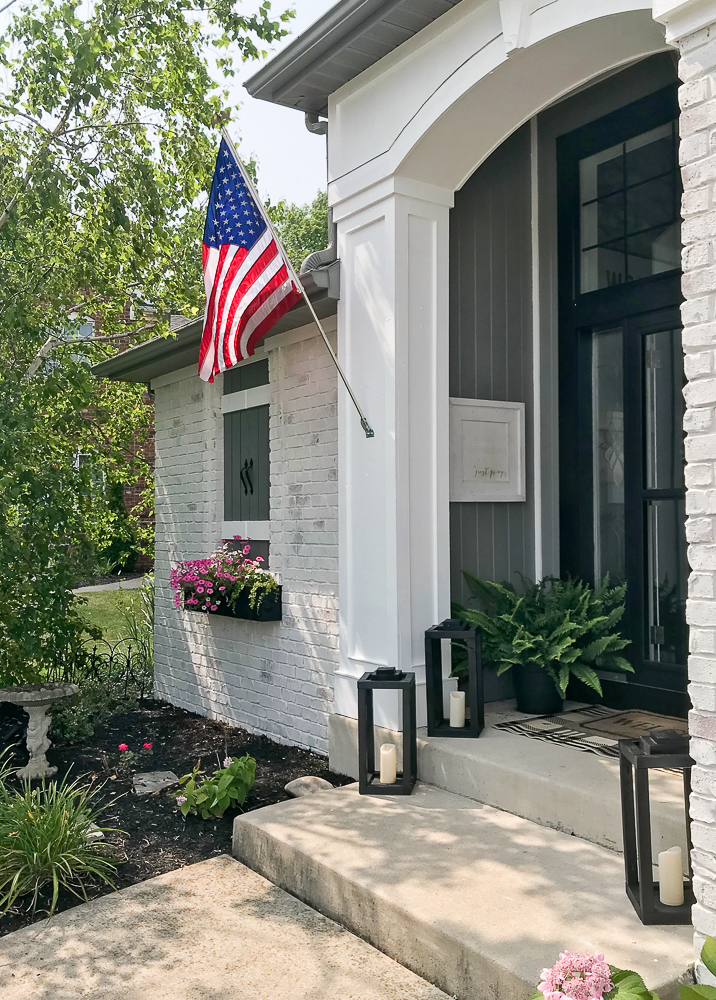 American flag on a pole attached to house