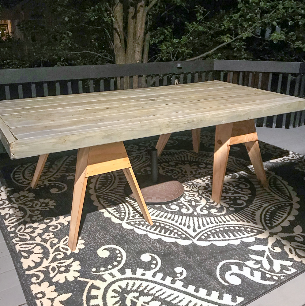 farmhouse table on a black opalhouse rug during a deck makeover