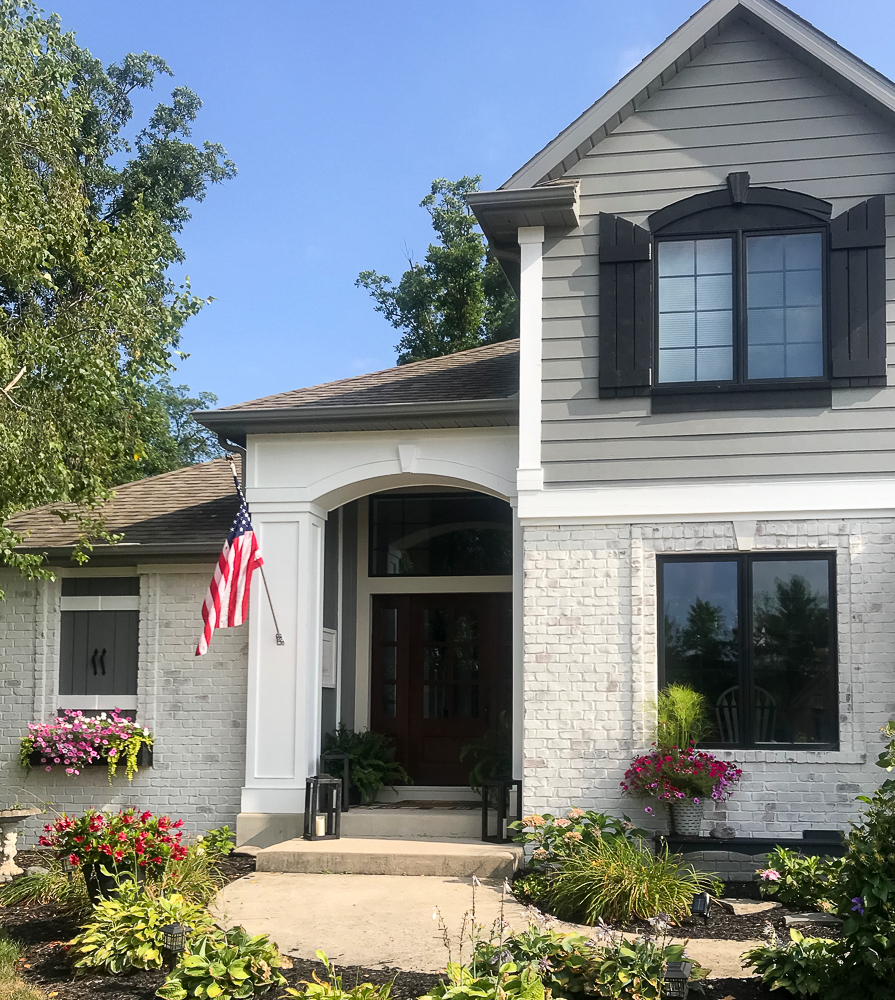 Craftsman home with American Flag and lots of pink flowers