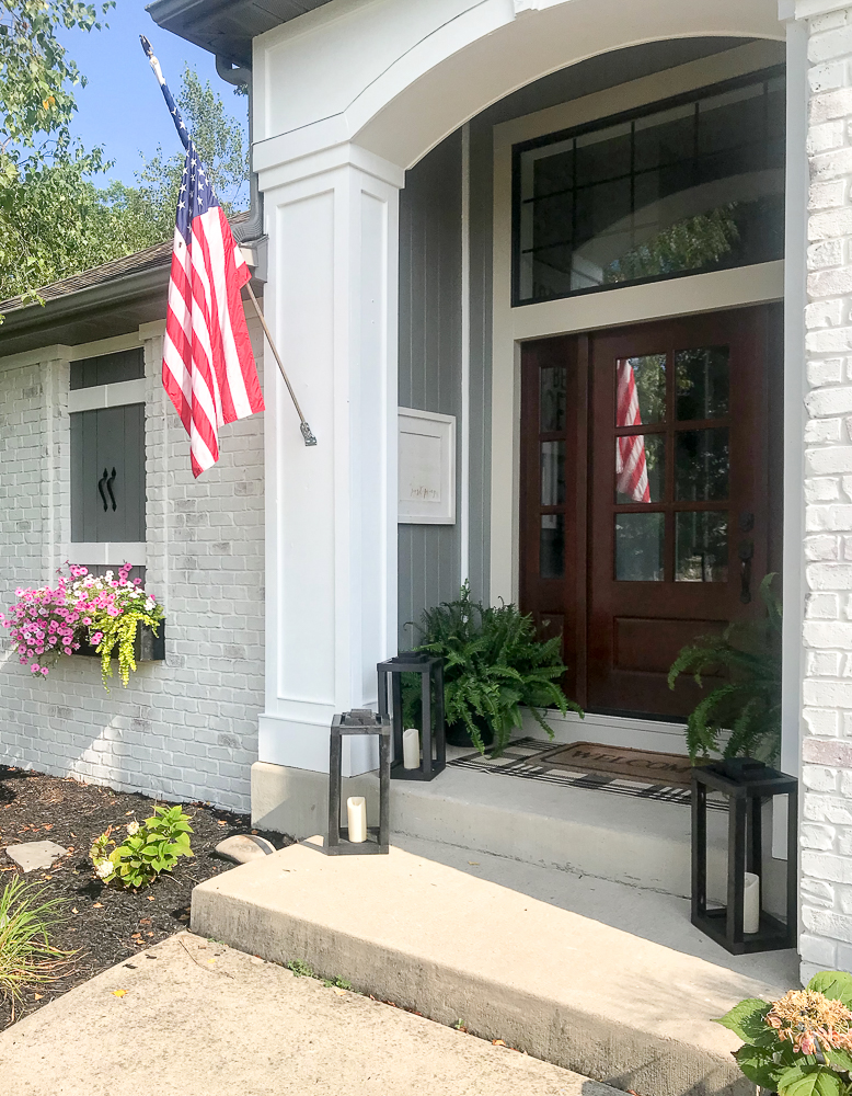 front of house with flower box and American Flag