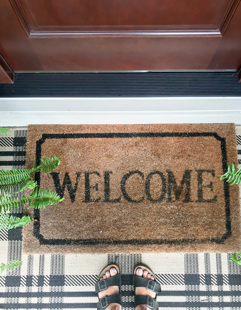 welcome mat layered with buffalo check rug