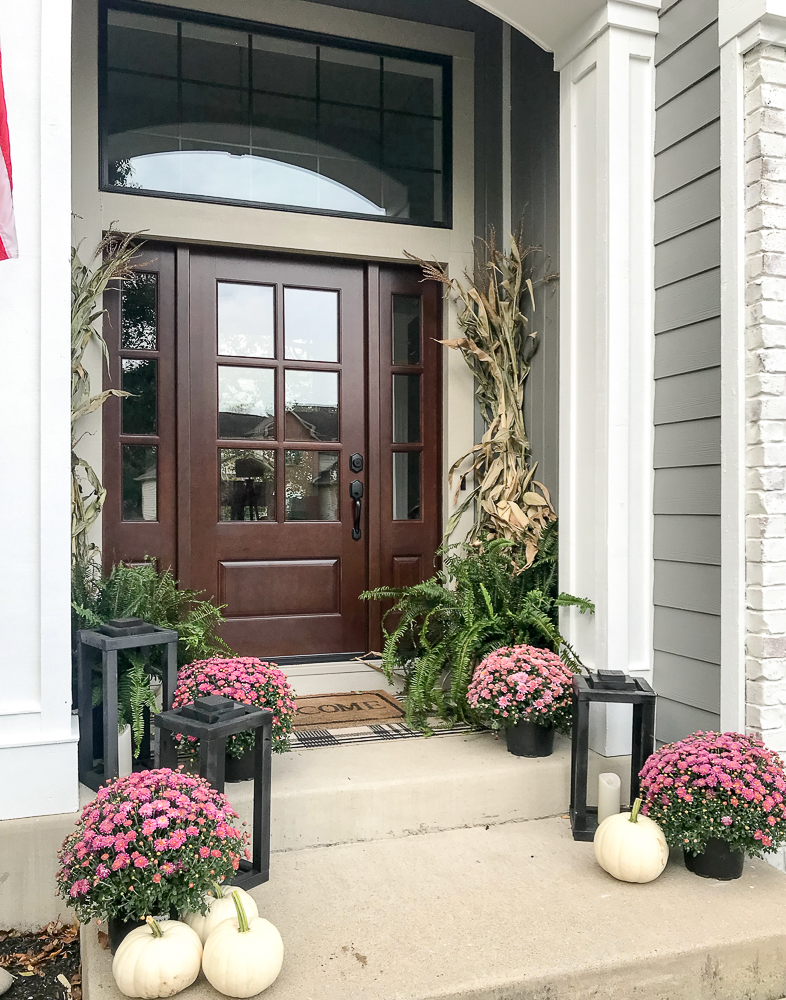 front door flanked with corn shocks, mums, ferns and lanterns and white pumpkins