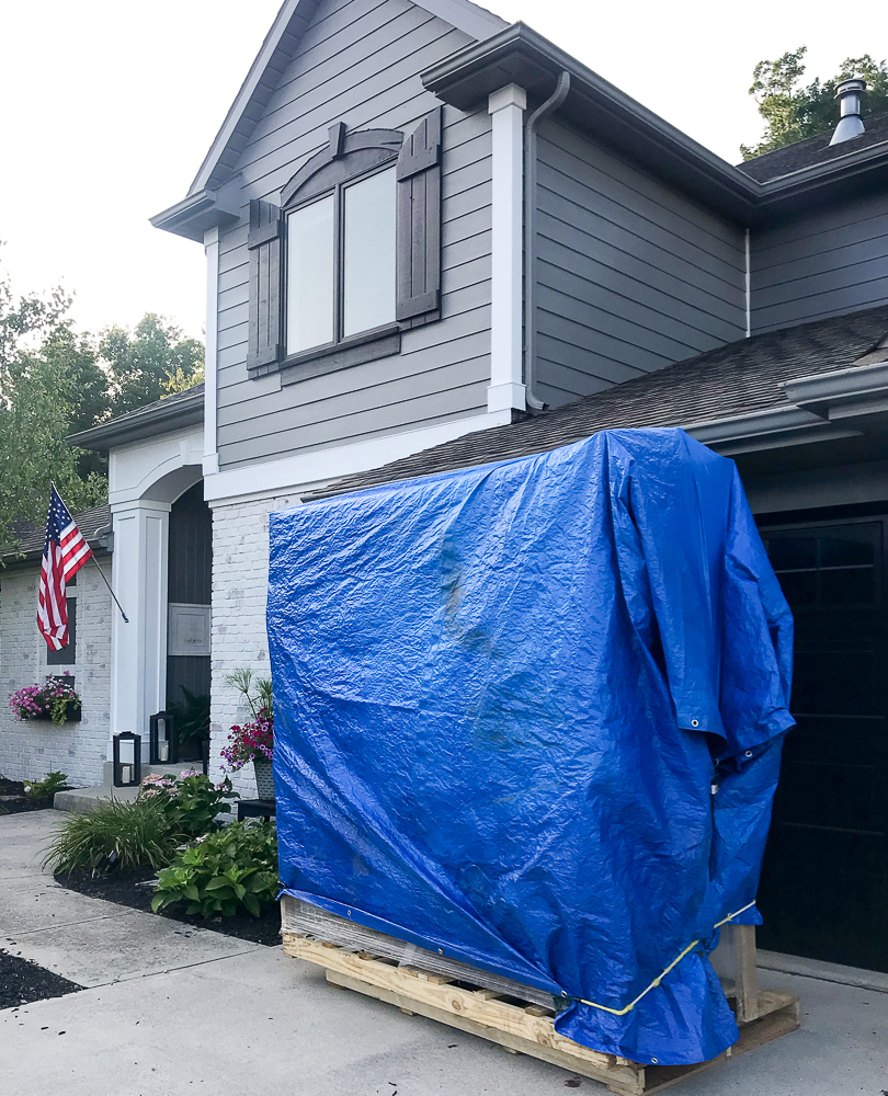 front door covered with a blue tarp in driveway