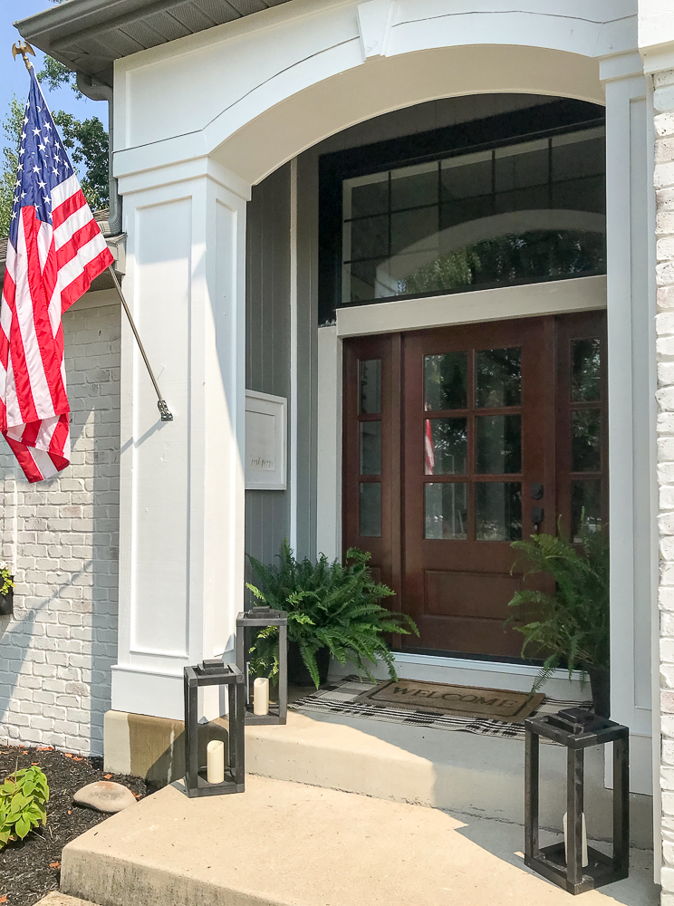 front porch with American Flag, lanterns and ferns