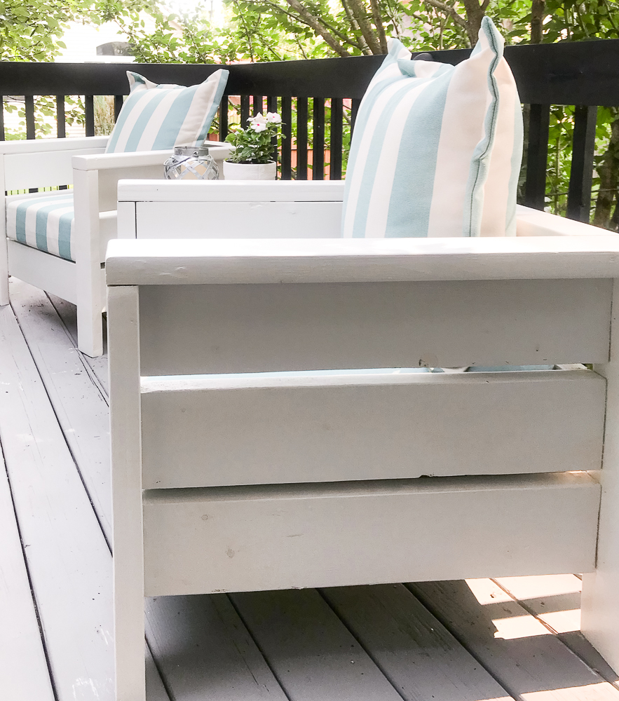 sideview of outdoor chairs on deck with striped blue cushions