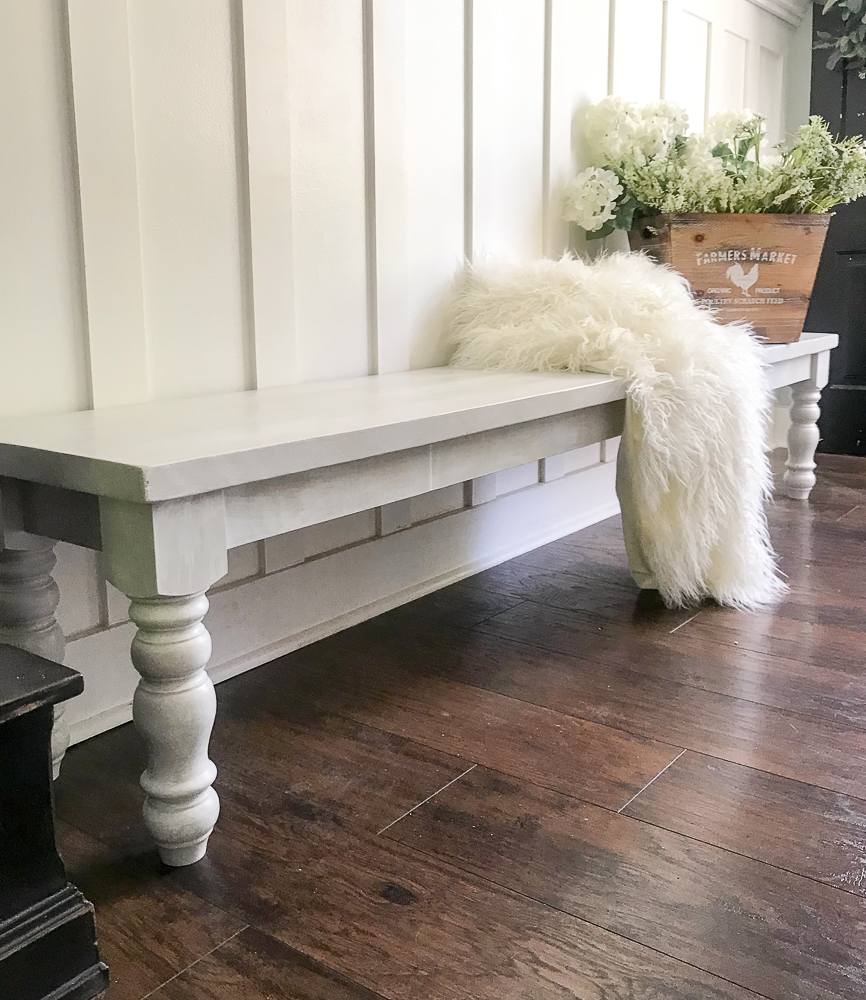farmhouse bench with white blanket and display of flowers on it