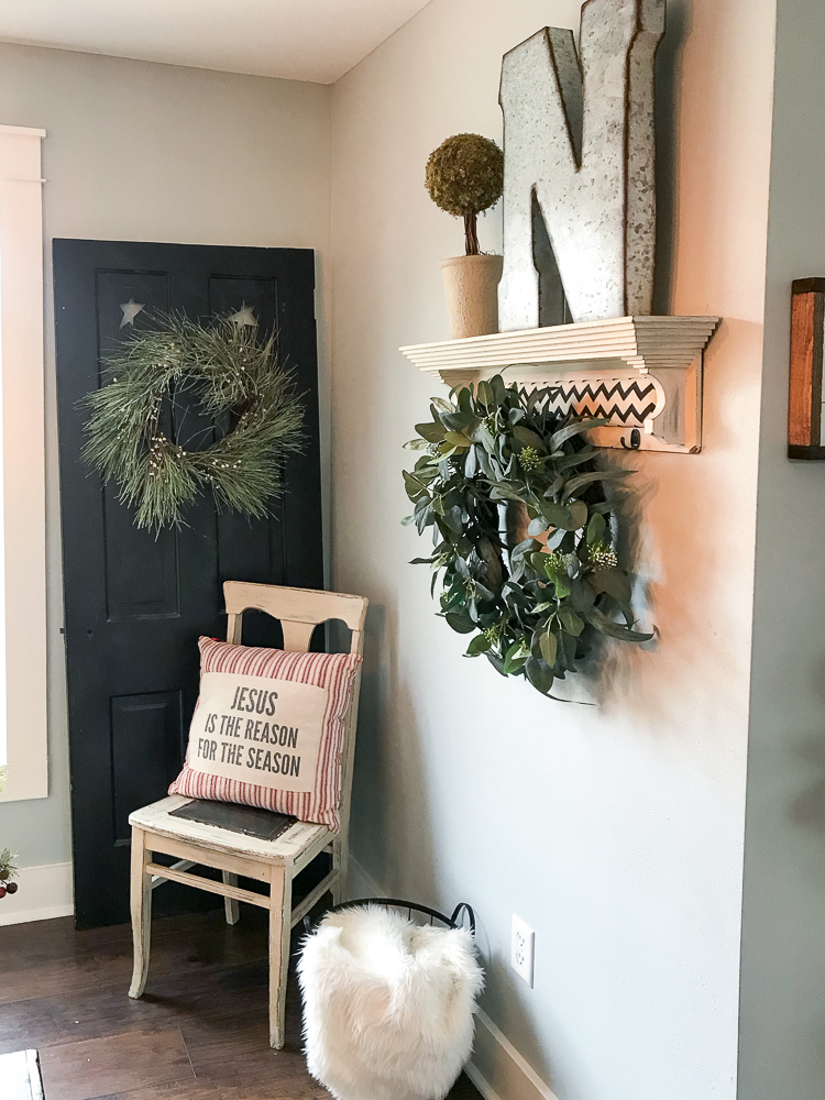chair with christmas pillow and black door behind it