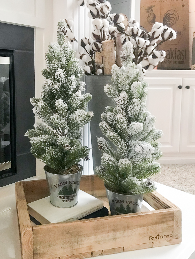 small Christmas trees on fireplace hearth