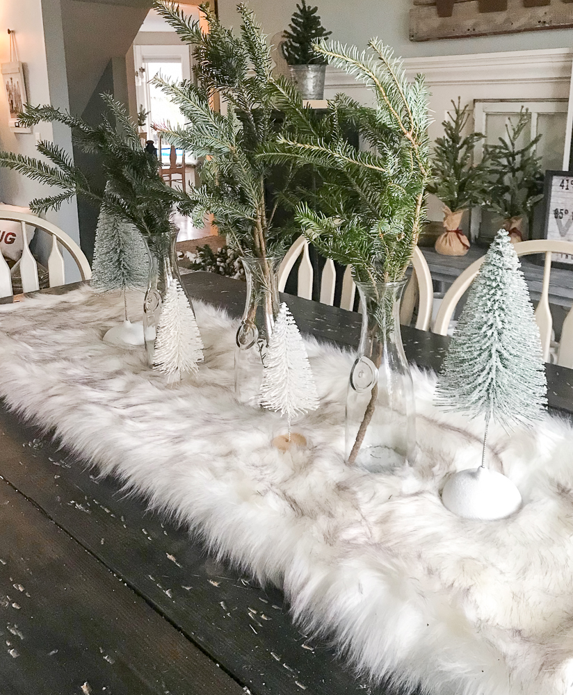 Christmas tablescape with mini trees and a soft blanket