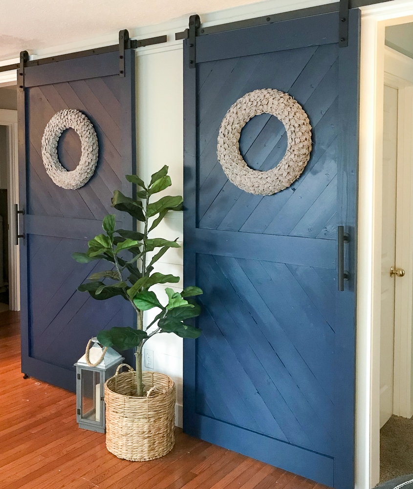 Two sliding barn doors with a fiddle leaf and lantern