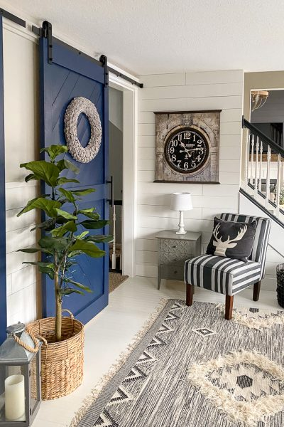 Sitting area on a boho style rug next to blue sliding barn doors