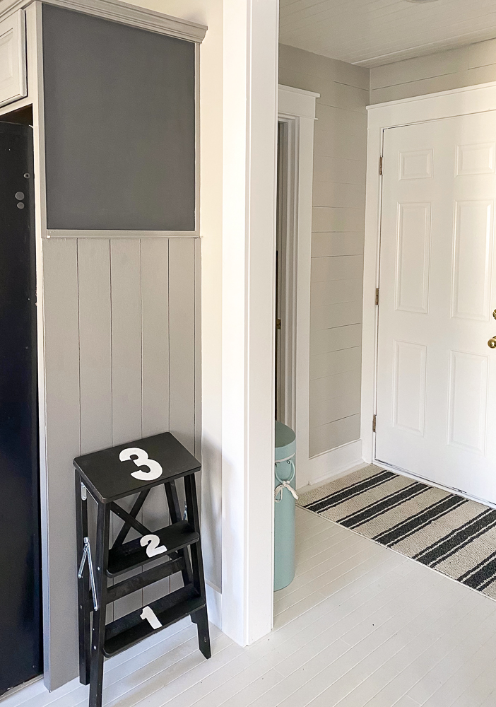 vertical shiplap with a black chalkboard and step stool