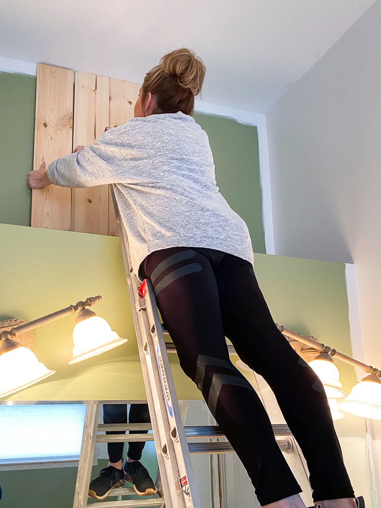 girl on ladder installing vertical carsiding for the master bathroom makeover project