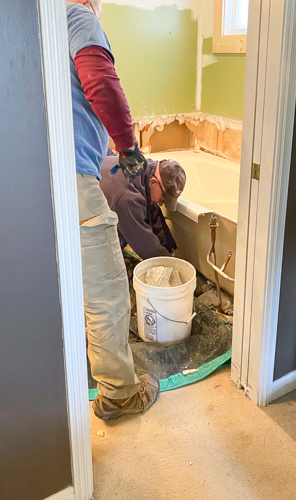 Two guys removing tub for master bathroom makeover plan