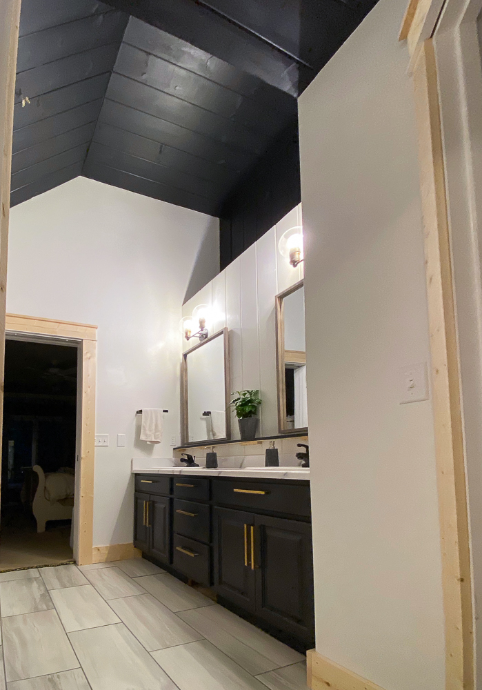 bathroom painted white with black ceiling and new tile flooring