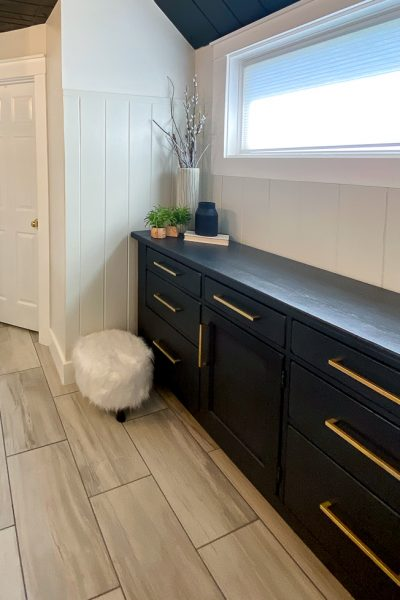 Black dresser with gold cabinet handles and white pouf