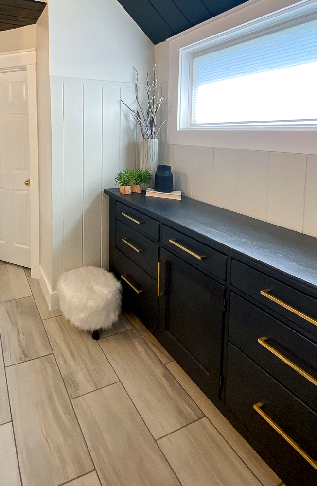Black dresser makeover with gold cabinet handles and white pouf