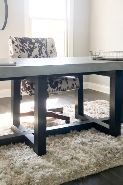 Large desk (gray and black) in a den with cow pattern chair