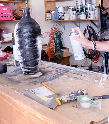 spray painting a black pot