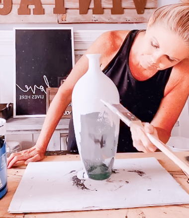 girl painting primer on glass vase