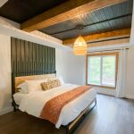 Large bedroom with king size bed and large pendant light along with black carsiding ceiling and ceiling beams
