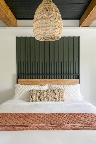 Beautiful bed with green accent wall behind it