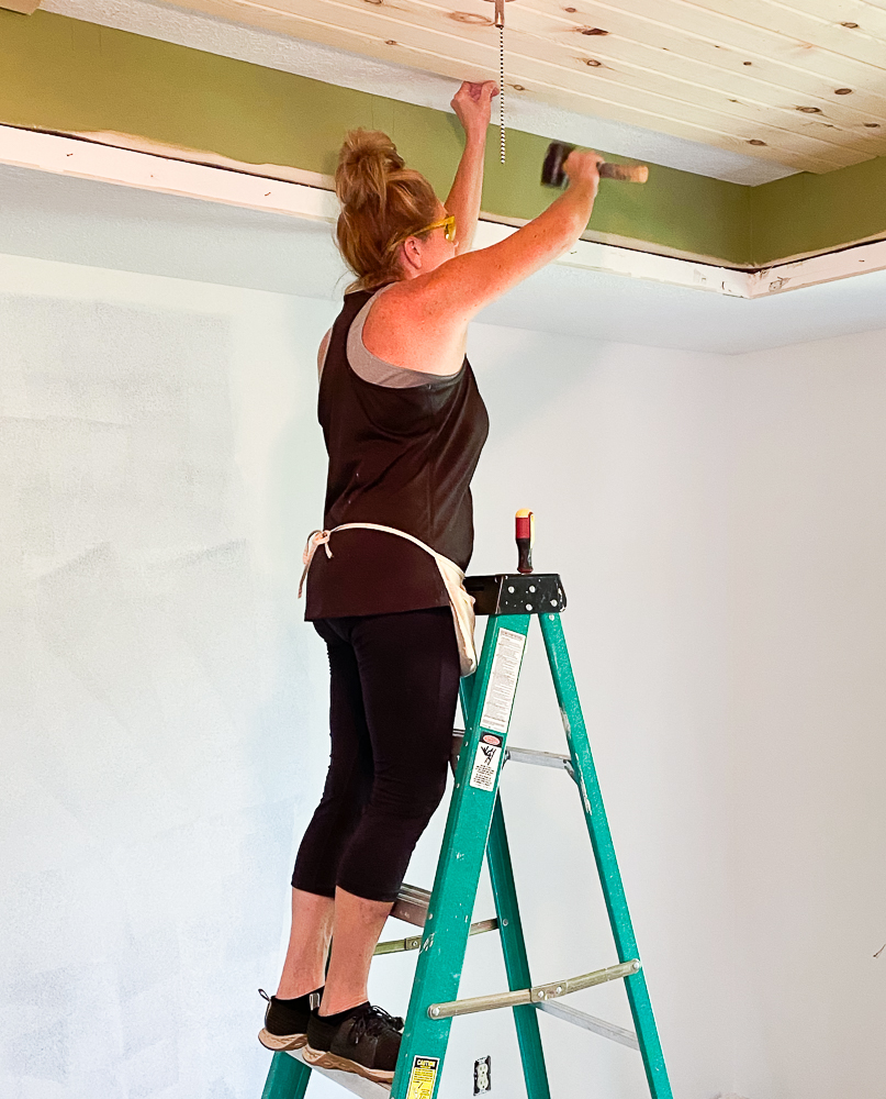 Girl standing on ladder diying a wood ceiling