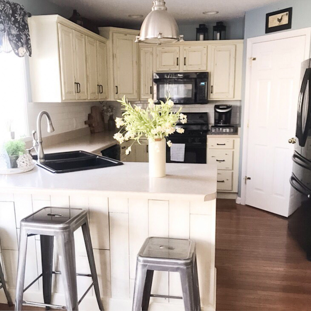 white kitchen with honey color hardwood floors before makeover projects