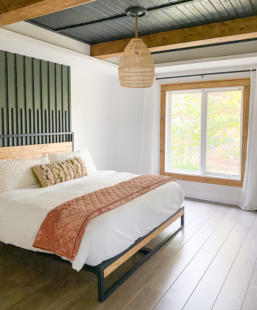 master bedroom with accent wall and stained window trim