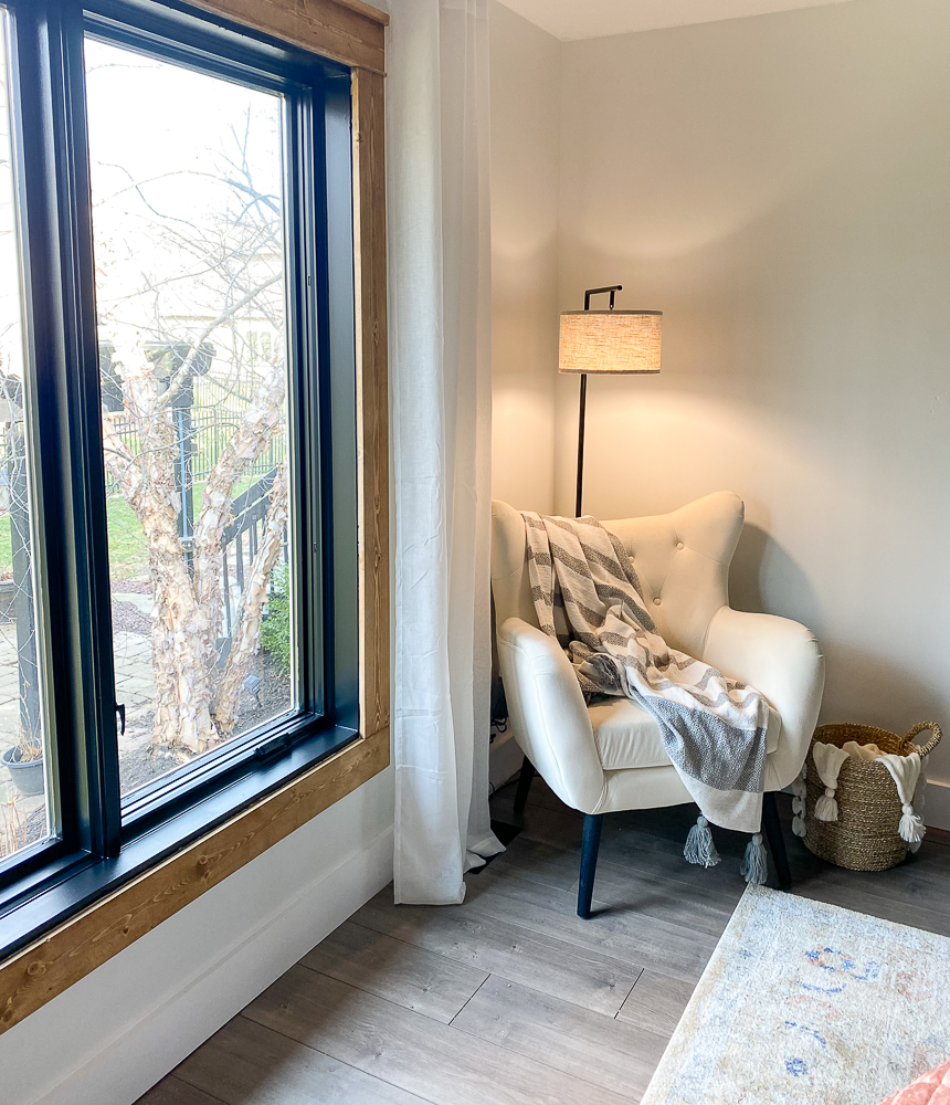 Cozy corner in master suite with wing chair and light
