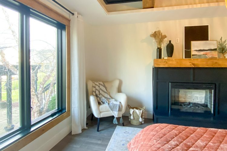 master bedroom with cozy corner with chair, blanket and fireplace next to it and craftsman trim throughout