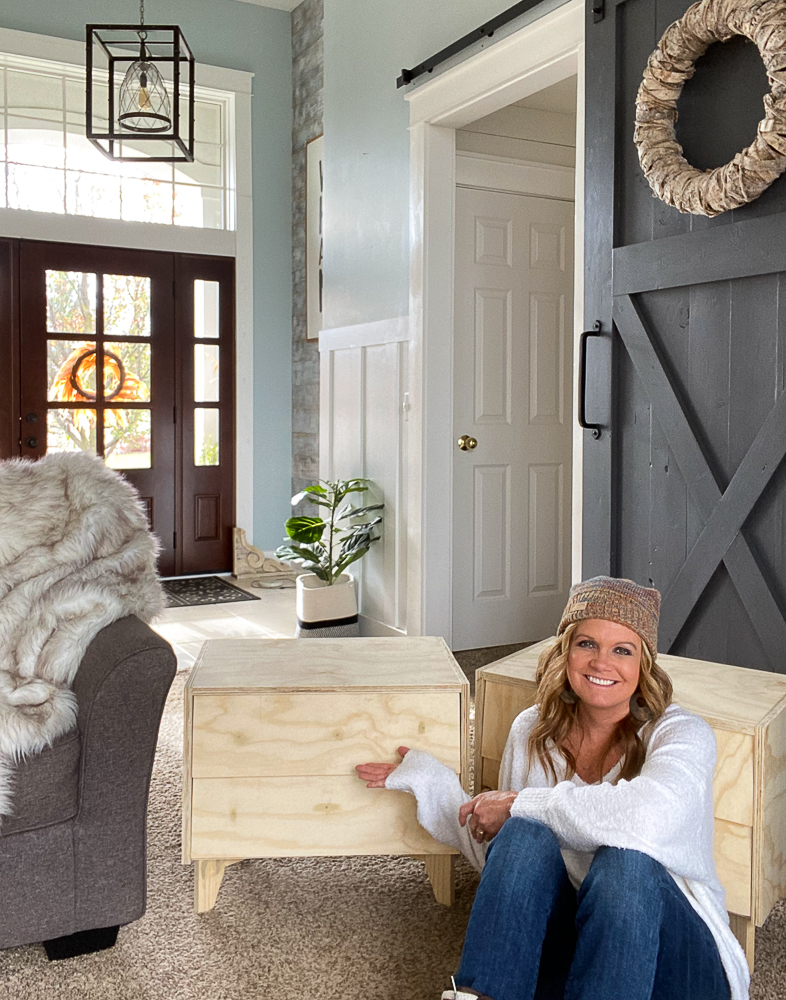 Woman sitting next to 2 newly built nightstands