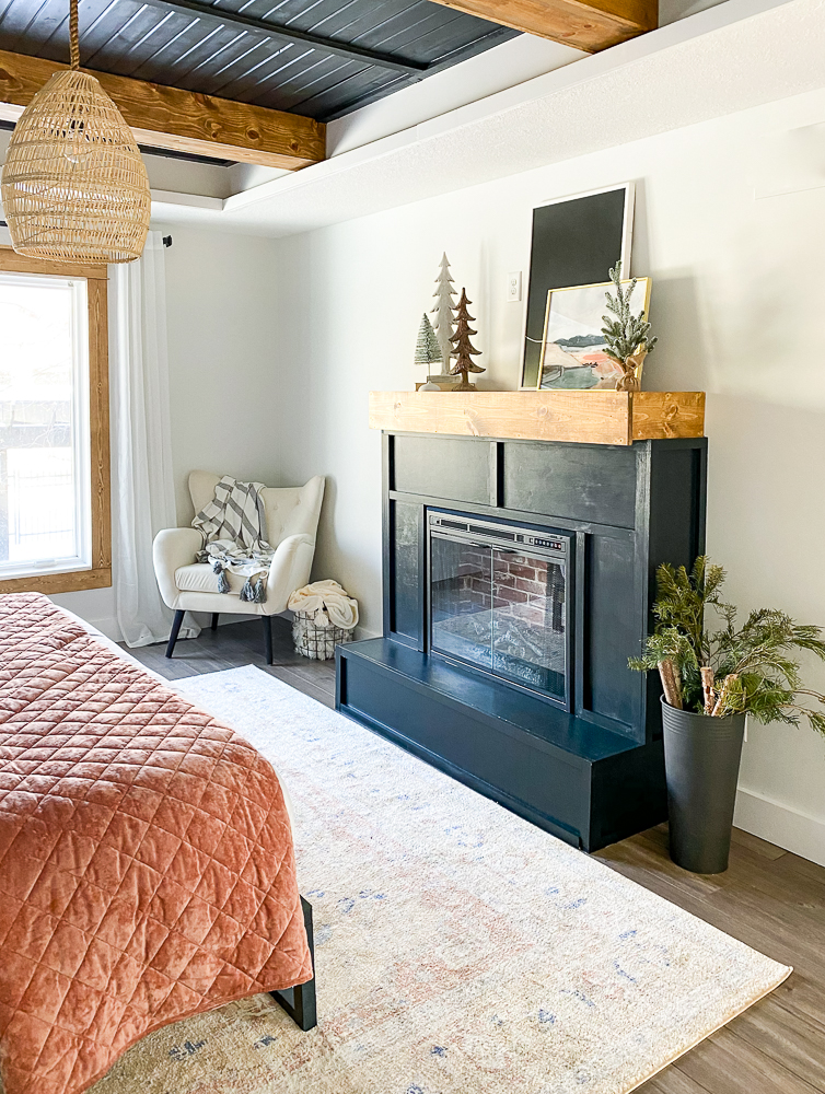 Master bedroom with electric fireplace surround and comfy chair