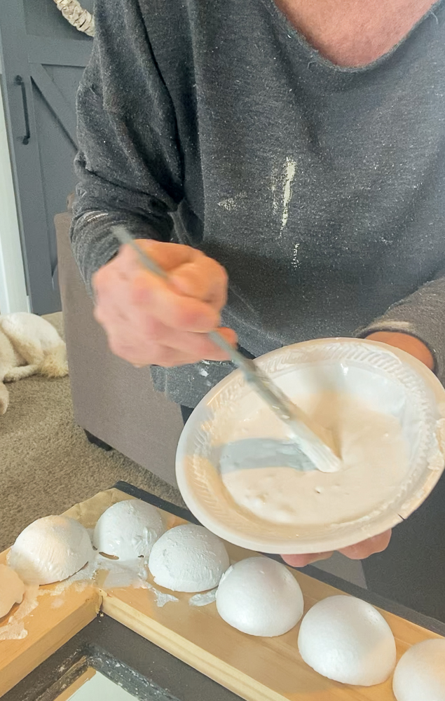 Woman mixing paint in bowl with paintbrush