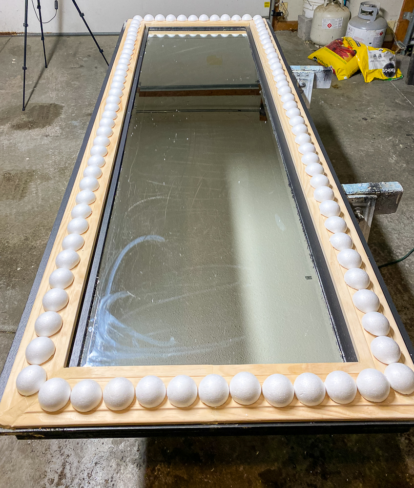 Mirror with wood frame and styrofoam balls around it