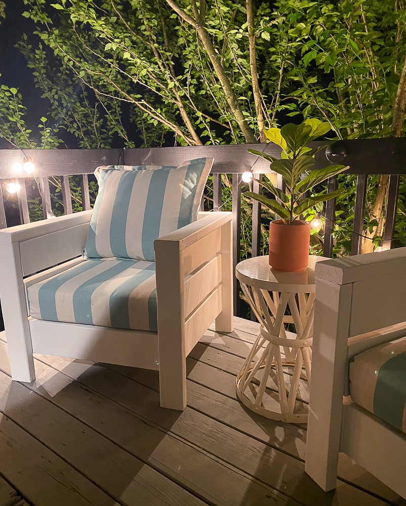 Night time view of sitting area on gray deck with a cute coffee table between two chairs