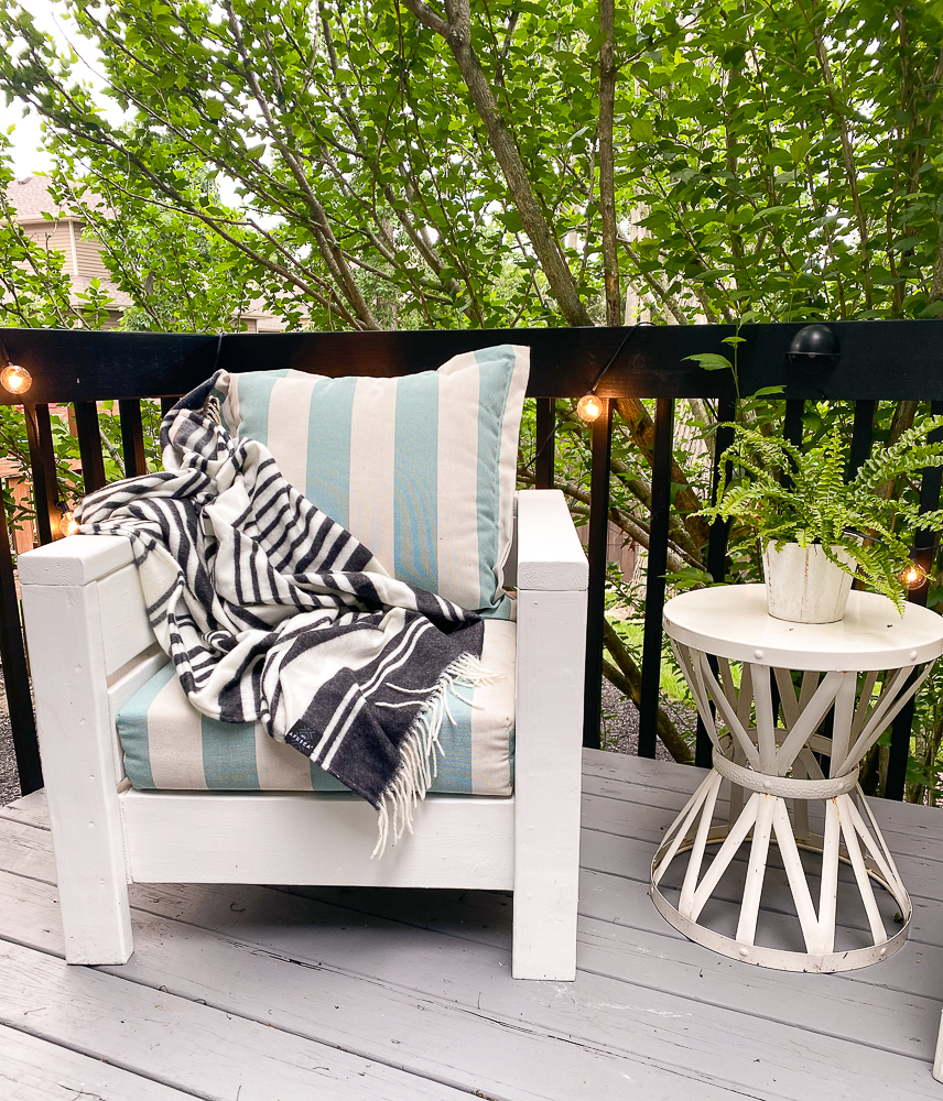White chair with striped cushions and blanket