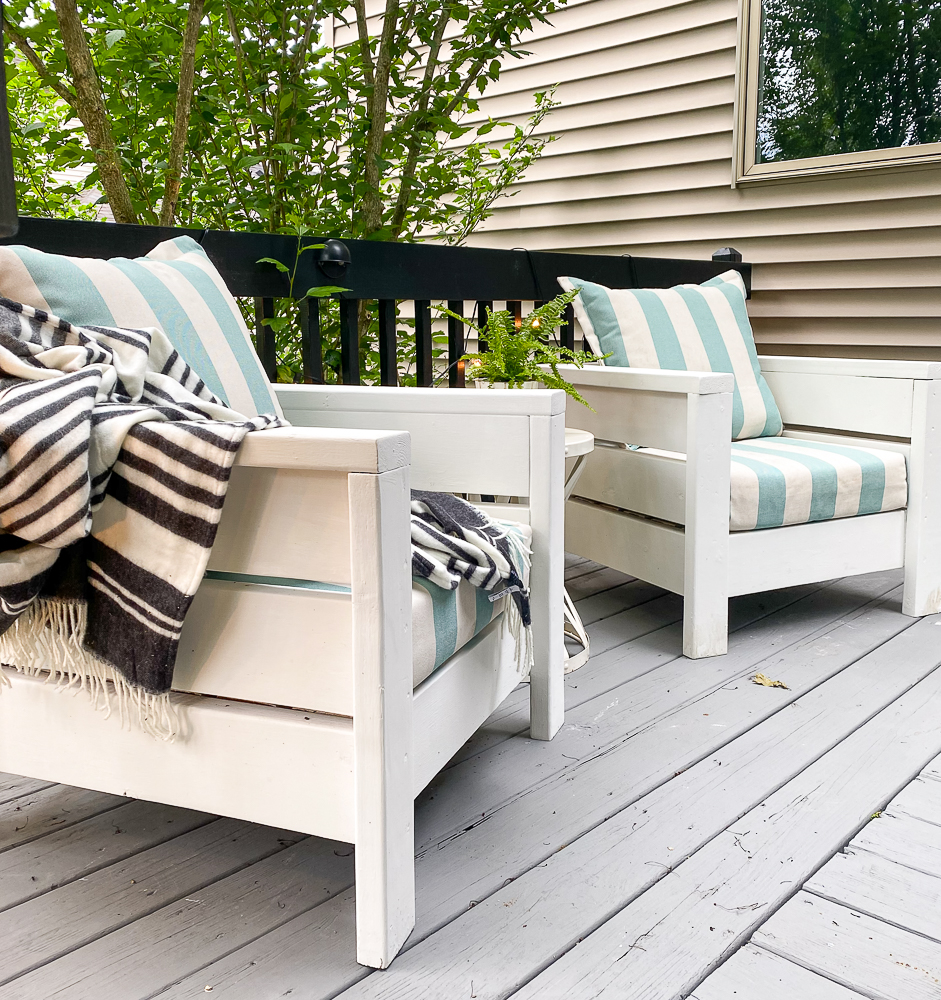 2 deck chairs with striped cushions and pillows on a gray deck
