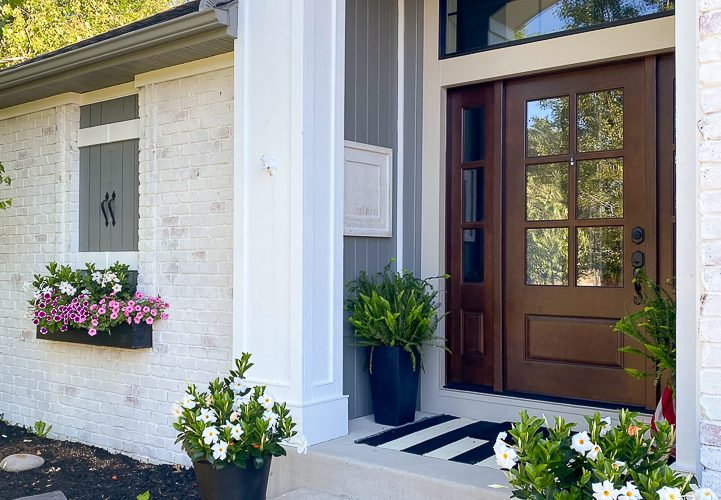 Front door of a white brick house with white flowers all around it